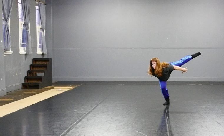 dancer in lunge in blue pants with other leg straight out behind her on angle upward