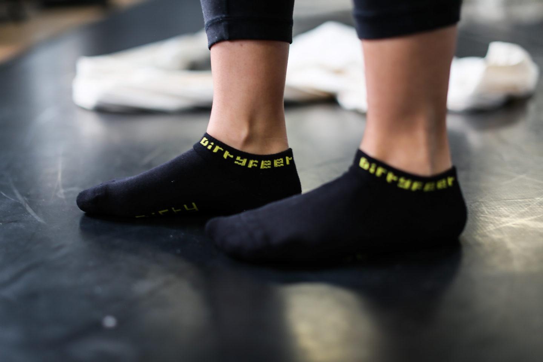 Dancer standing wearing black DirtyFeet ankle socks